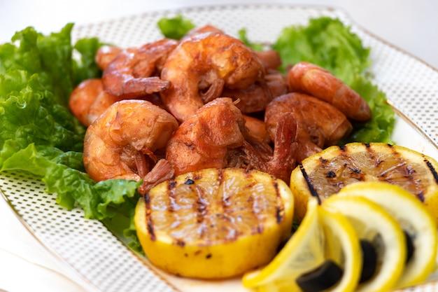 Креветки гриль с лимонным грилем на белой тарелке