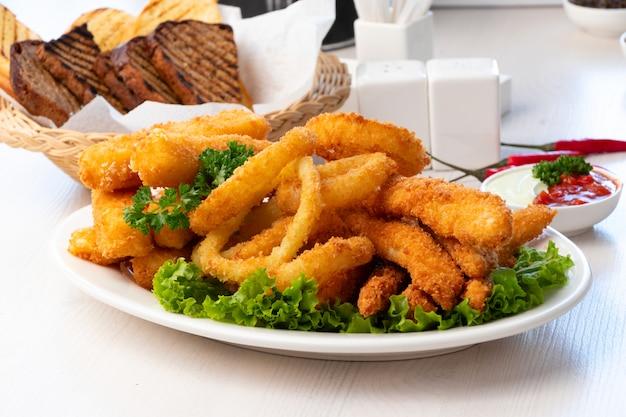Жареные кольца кальмаров с сырными палочками на белой тарелке