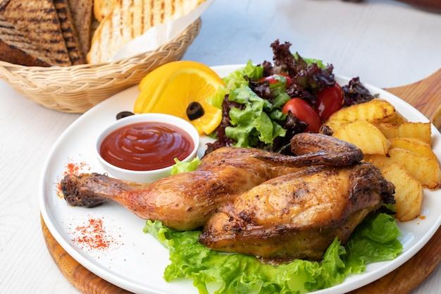 Жареная курица с картофелем и свежим салатом на белой тарелке
