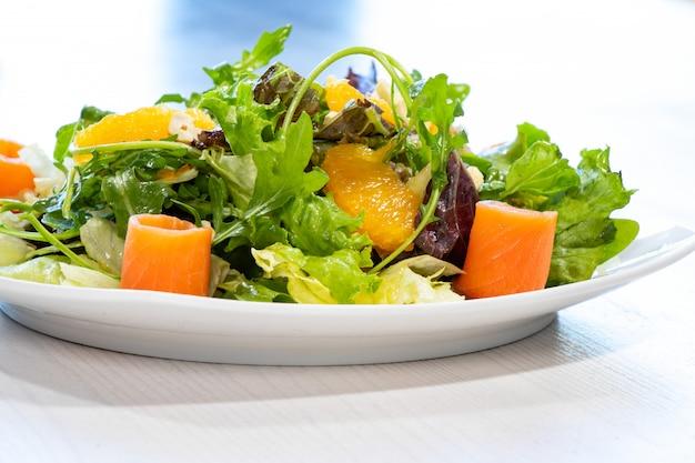 Свежий летний салат с зеленью, орехами, апельсином и тунцом на белой тарелке