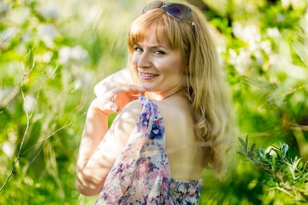 緑豊かな公園で素敵なサンドレスといちゃつく笑顔で美しい金髪の女性