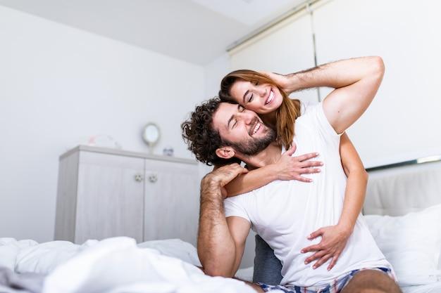 ベッドで彼女のパートナー、感情と愛を示すベッドで幸せなカップルを抱きしめる女性。美しい愛情のあるカップルがベッドでキスします。一緒にベッドに横たわっている美しい若いカップル。