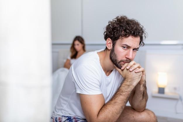 ガールフレンドと議論した後悲しい思いやりのある男。関係の難しさ、紛争、家族の概念、寝室で問題を抱えている不幸なカップル。ベッドに座って悲しい男