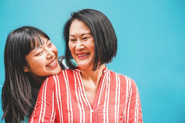 Азиатские мать и дочь весело на открытом воздухе - счастливые люди семьи, наслаждаясь время вместе