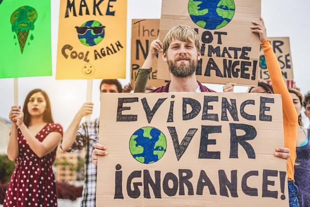 道路上のデモ隊のグループ、さまざまな文化や人種の若者が気候変動-地球温暖化と環境のコンセプト-金髪の男の顔に焦点を当てるために戦う