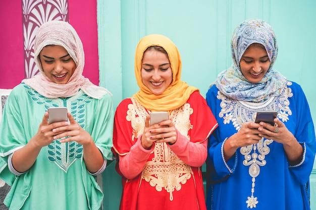 屋外のスマートフォンを使用して幸せなアラビアの友人-新しいトレンド技術を楽しんでいる若いイスラム教の女の子-インフルエンサーと友情のコンセプト-顔に焦点を当てる