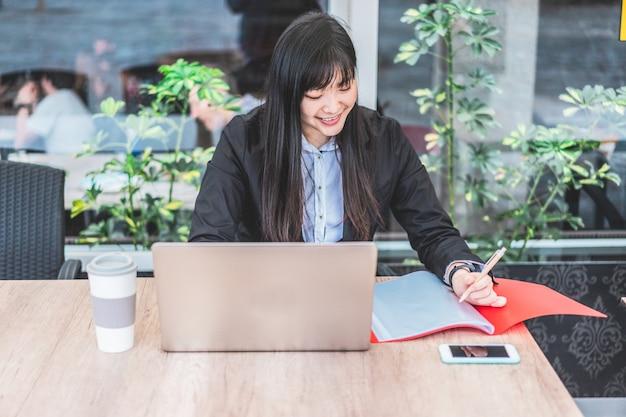 Азиатская женщина-предприниматель работает и пьет кофе в офисе - деловая молодая женщина сидит за партой в коворкинг-пространстве. технология и концепция работы - сосредоточиться на лице девушки