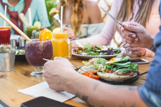 ブランチを食べたり、プラスチック製の無料バーレストランで生態学的なストローでスムージーボウルを飲んだりする若者の手ビュー