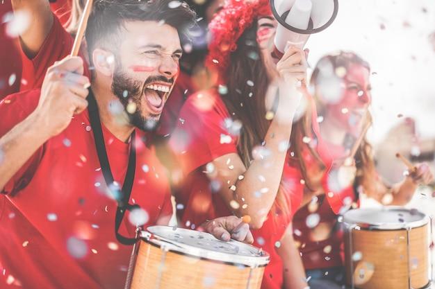 サッカーサポーターのファンがスタジアムでサッカーの試合イベントを見て紙吹雪で応援