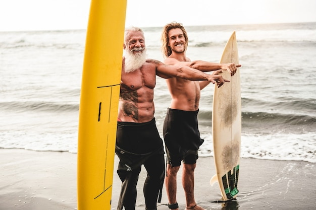 熱帯のビーチでサーフィンに行く多世代の友人