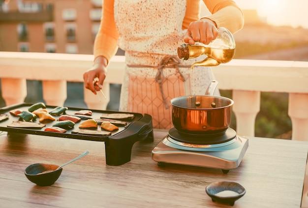 若い女性は屋外のテラスのテラスで夕食を準備しながら野菜をグリルします。