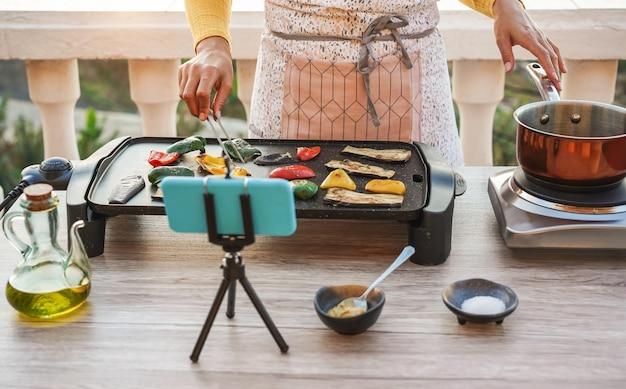 若い女性シェフが自宅でウェビナーマスタークラスレッスンのオンラインストリーミング中に屋外で料理
