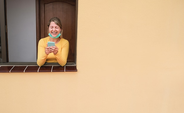 自宅でのロックダウン検疫中に携帯電話を使用して幸せな女の子-技術動向を楽しみながら窓にもたれて若い女性-顔に焦点を当てる-コロナウイルス防止の概念