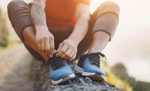 フィットタトゥー男がジョギングセッション中に屋外の彼のスポーツの靴を結ぶ