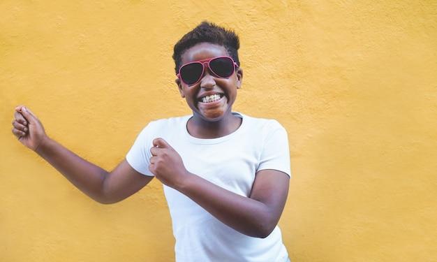 屋外のサングラスを着て踊るアフリカの男性の子供。黄色を楽しんでいる黒のアフロの子供
