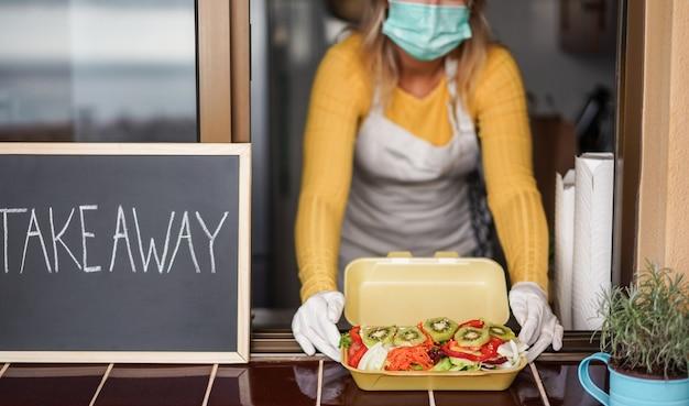 若い女性がコロナウイルスの発生時にレストラン内で健康的な持ち帰り用の食品を準備する-オンライン注文サービスのためにベジタリアンフードを調理するキッチン内の労働者