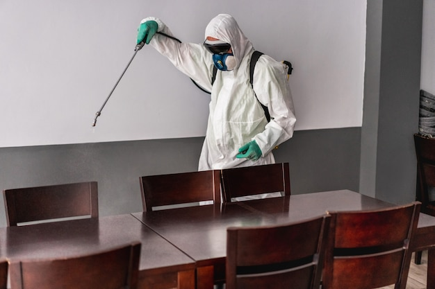 Рабочий в защитном костюме в защитной маске при дезинфекции в баре-ресторане