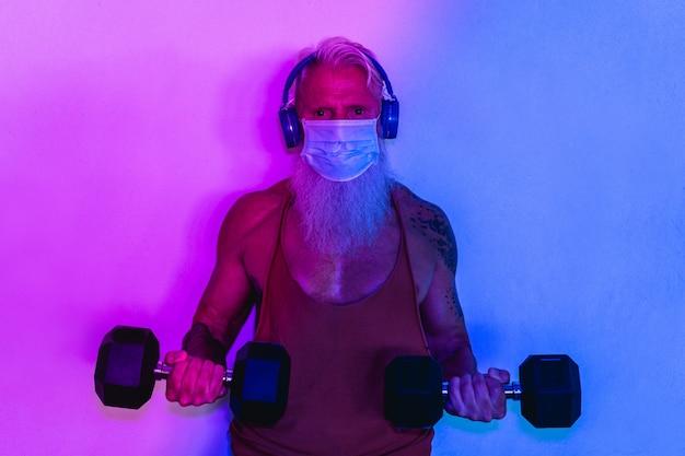Старший мужчина делает тренировки с гантелями во время ношения защитной маски для лица