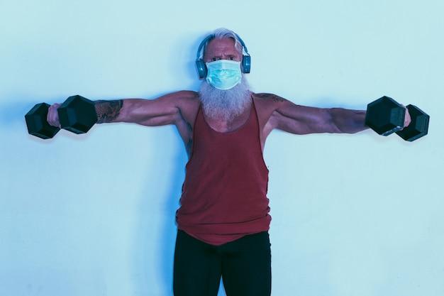 顔の防護マスクを着用しながらダンベルでジムのトレーニングを行うシニア男性
