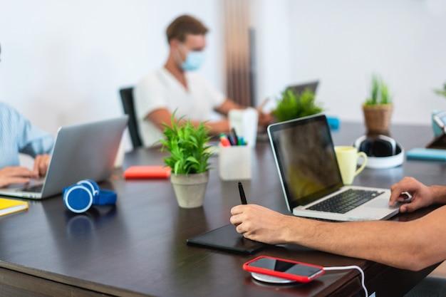 コロナウイルス拡散防止-社会的距離、技術、スタートアップのコンセプト-クローズアップの手に焦点を当てるための防護マスクを着用しながらコワーキングクリエイティブオフィス内で働く若者たち