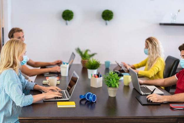 コロナウイルス拡散防止のための保護マスクを着用しながらコワーキングクリエイティブオフィス内で働く若者たち