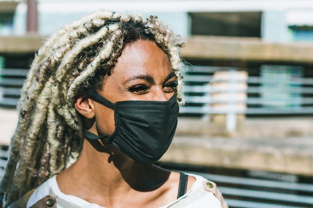 顔の防護マスクを着ている金髪のドレッドヘアを持つアフリカの少女の肖像画