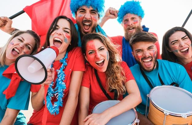 Сумасшедшие фанаты спорта играют на барабанах и кричат, поддерживая свою команду - футбольные болельщики веселятся на футбольном матче на стадионе - концепция мероприятия - сосредоточьтесь на лицах левой девушки