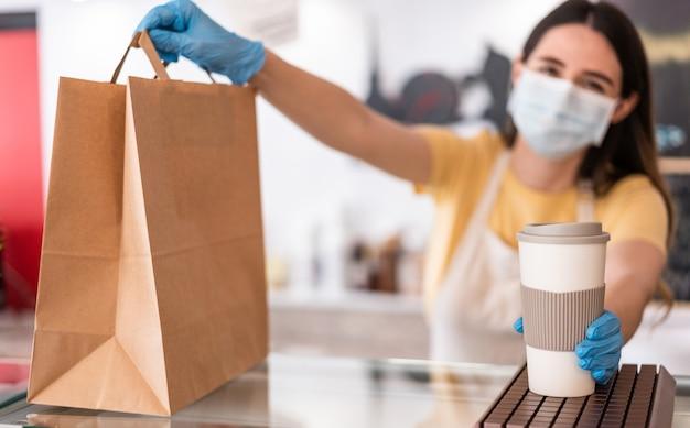 Молодая женщина в маске во время сервировки завтрака и кофе в кафетерии ресторана - работник, готовящий доставку еды в пекарню в период коронавируса - фокус на правой руке