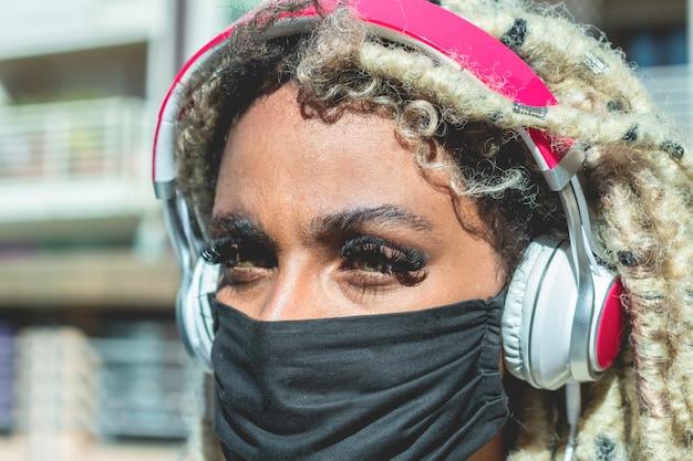 ブロンドのドレッドヘアを持つアフリカの女の子がコロナウイルス防止のための顔の保護マスクを着用しながら音楽を聴く