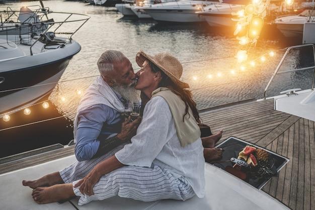 Пожилые супружеские пары, имеющие нежные моменты на старинной парусной лодке
