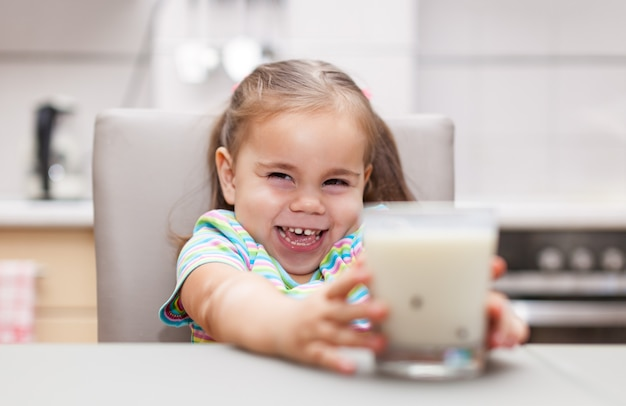 自宅の台所でミルクを飲む子供