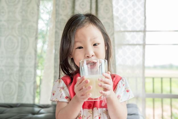 ガラスからミルクを飲む小さなアジアの女の子