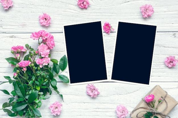 空白のフォトフレームとギフトボックスとピンクのバラの花の花束