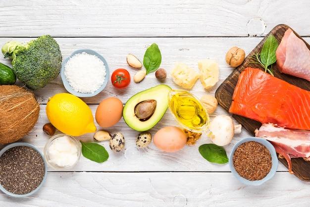 Кетогенное диетическое питание. здоровые продукты с низким содержанием углеводов. кето диета концепции. овощи, рыба, мясо, орехи, семена, масло, сыр