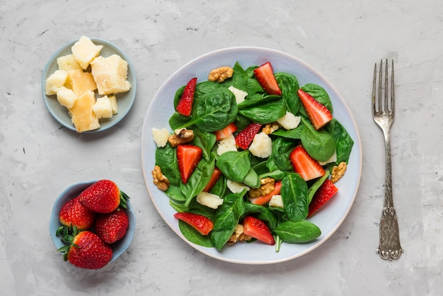 Салат из свежей клубники с листьями шпината, сыром пармезан и грецкими орехами с вилкой. здоровое диетическое питание