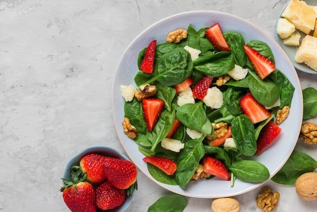 イチゴ、ほうれん草の葉、パルメザンチーズ、クルミのコンクリートテーブルのサラダ。健康的なダイエット食品