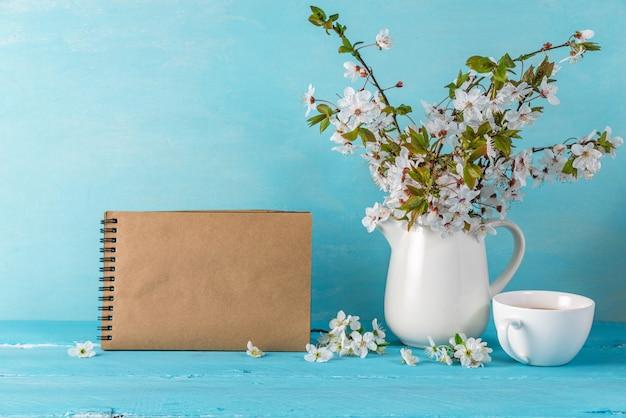Натюрморт с красивыми весенними цветами сакуры, чашка кофе и чистый лист бумаги тетради.