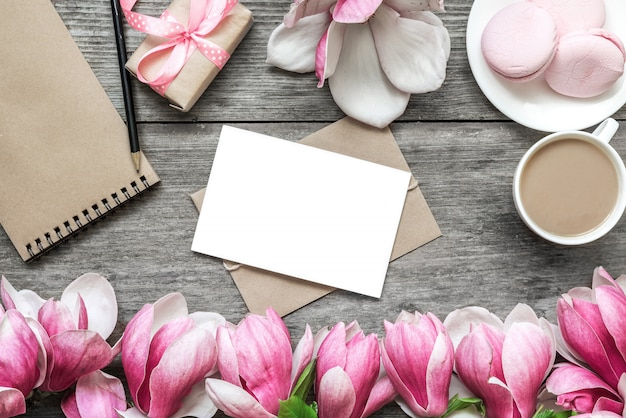 空白のグリーティングカード、カップのカプチーノ、マカロン、ギフトボックス、紙のノート、マグノリアの花