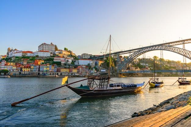 ポルト、ポルトガルワイン樽と橋のある伝統的なラベロ船とドウロ川の旧市街の街並み