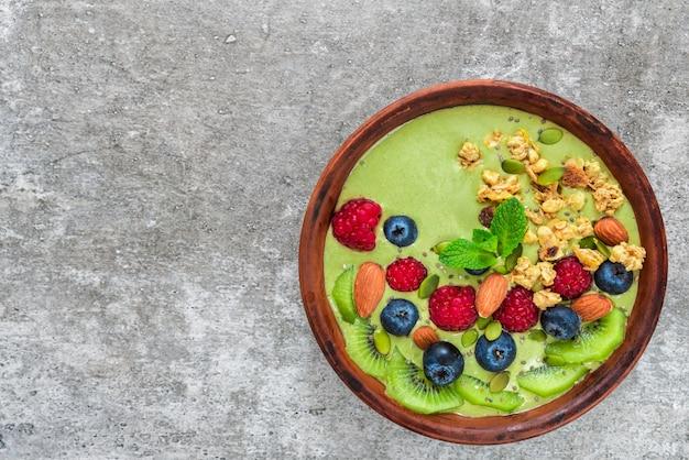 健康的なビーガン朝食のための新鮮なベリー、フルーツ、グラノーラ、ナッツ、種子を含む緑の抹茶スムージーのボウル