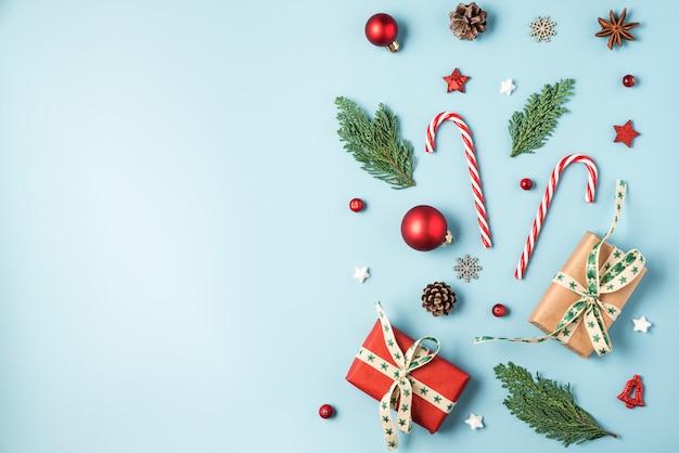 クリスマスの背景。モミの木の枝、ギフトボックス、赤い装飾、キャンディ、松ぼっくり