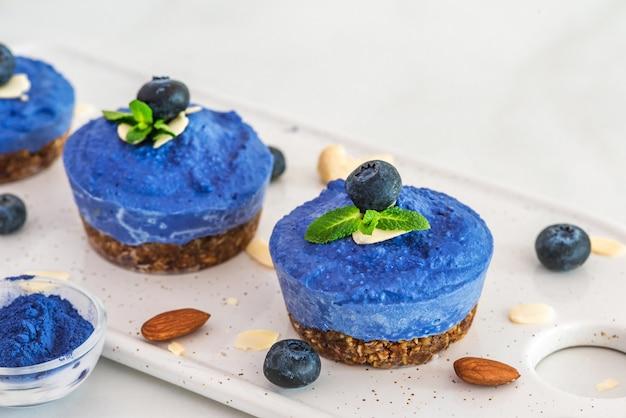 生のブルーベリー、アサイ、蝶エンドウ豆の花のビーガンチーズケーキ、新鮮なベリー、ミント、ナッツ。健康的なビーガンフードコンセプト