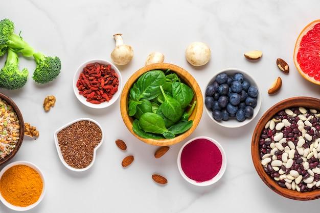 Суперпродукты в виде овощей, асаи, куркумы, фруктов, ягод, грибов, орехов и семян. здоровая веганская еда