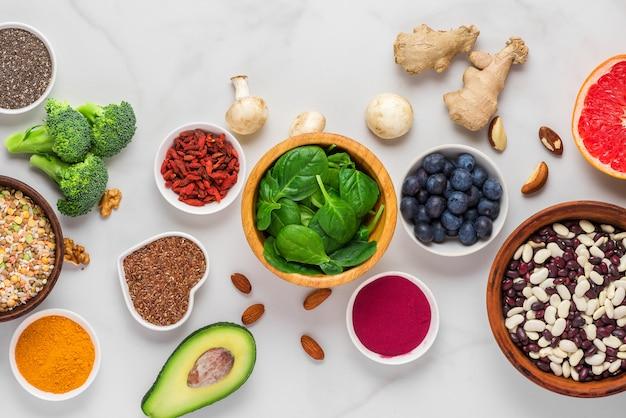 白い大理石のテーブルのスーパーフード。野菜、アサイ、ウコン、果物、果実、ナッツ、種子。健康食品