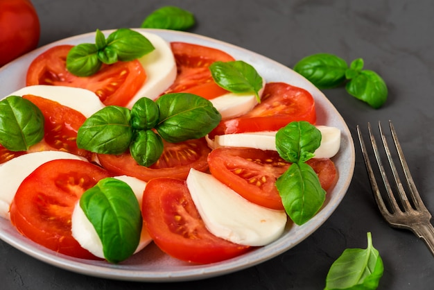 Салат капрезе со спелыми помидорами и сыром моцарелла, свежими листьями базилика. итальянская еда
