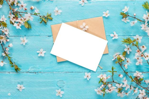青い木製のテーブルに春の桜の花を持つ空白のグリーティングカード。平干し。上面図。モックアップ。春のコンセプト