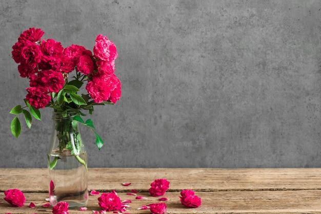 Букет красных роз в вазе с бутонами вокруг.