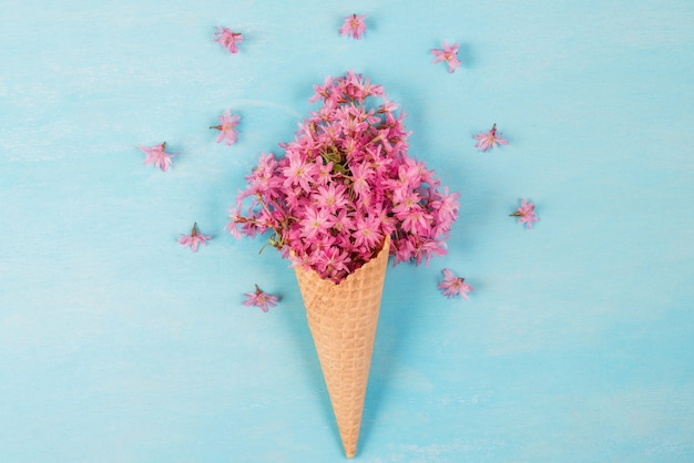 春の花ピンクの桜または桜の花とアイスクリームコーン。最小限の春のコンセプト。平置き