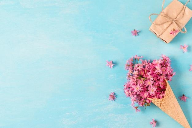 ギフト用の箱とワッフルコーンで春のピンクの桜の花。最小限の春のコンセプト。平置き