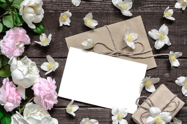 ギフトボックスとジャスミンの花で作られたフレームにピンクと白のバラで空白の白いグリーティングカード